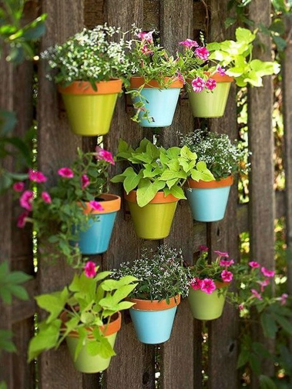 Coloured pots hanging from wooden pallets