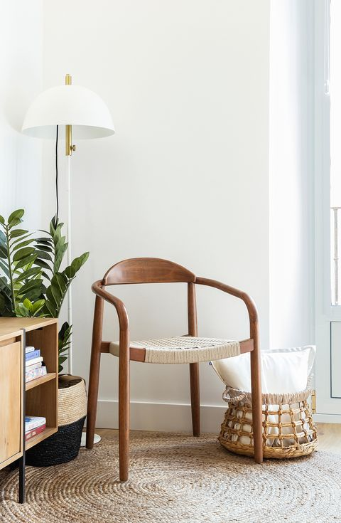 reading corner with wooden chair, white floor lamp and a basket of natural fibres