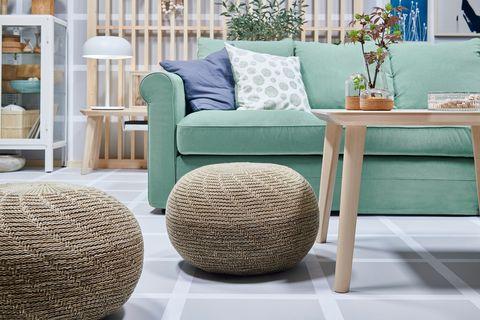 green sofa next to poufs of natural fibres