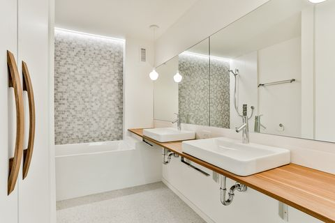 bathroom decorated in white with a contemporary design with a bathtub and a floating wooden shelf