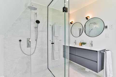 construction site shower with a modern design floating sink unit and two round mirrors