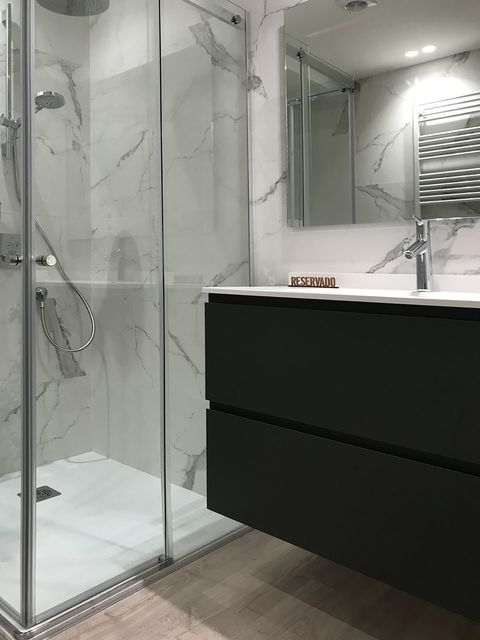 bathroom with a built in shower and a black floating washbasin unit