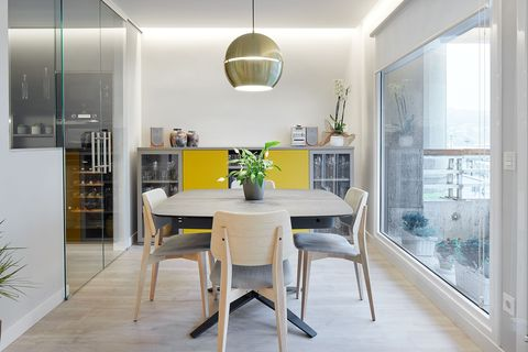modern design dining room with wooden table and chairs and golden ceiling lamp