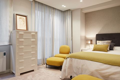 modern bedroom decorated in neutral tones with mustard details