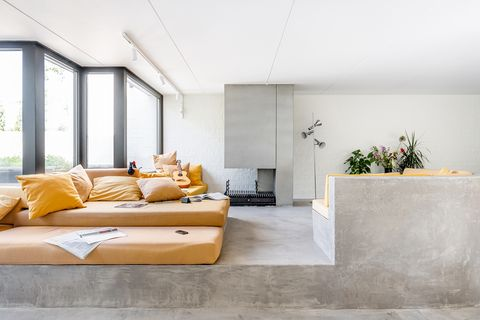 living room with concrete floor and sofa structure and orange seats