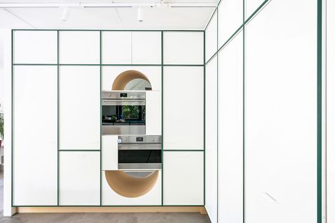 kitchen cabinets in white with green gaskets and oven and microwave in column