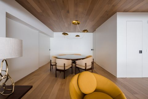 contemporary design dining room with round table and mustard-coloured upholstered chairs