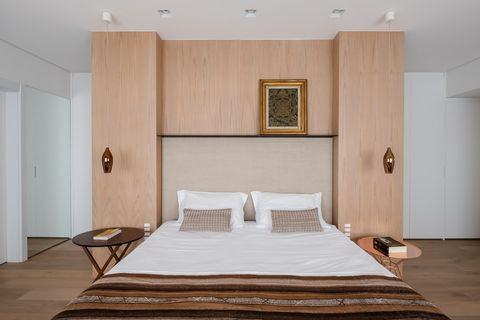 bedroom with a wooden headboard that acts as a room divider