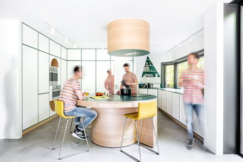 modern kitchen designed in white with green joints and a central wooden island that acts as a dining table