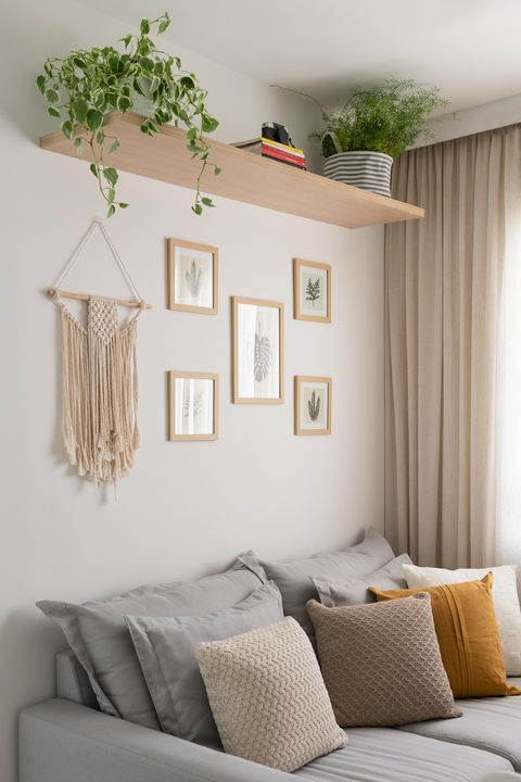 grey sofa with cushions and wall decorated with botanical illustrations and macramé