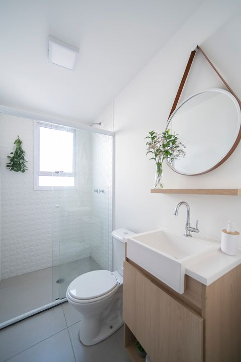 bathroom decorated in white with wooden furniture and plants