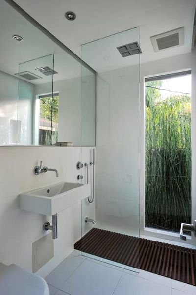 Bathroom with white walls and floor, with mirror that covers the entire wall