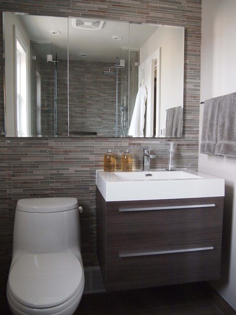 Wall on which a washbasin with wooden cabinet, toilet and large mirror is installed.  Tiles in different shades of brown and gray