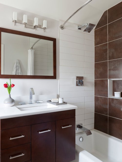 Bathroom with white walls and ceiling, shower wall in dark brown to create depth