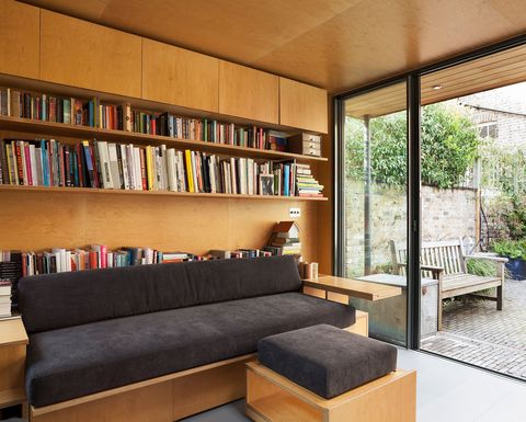 bookcase with books behind a sofa with matching footrests