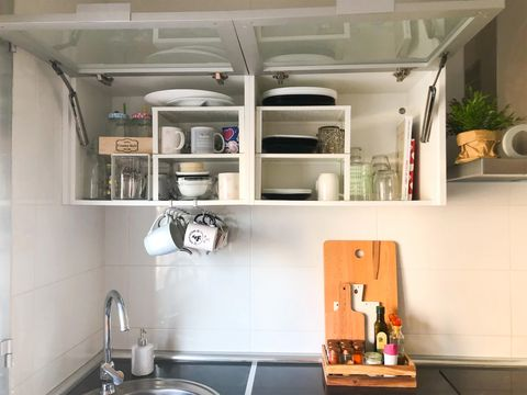 cupboard with dishes over the sink
