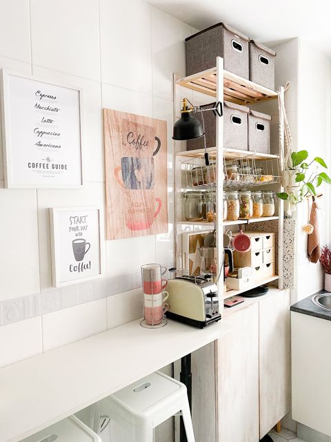 small kitchen decorated in white with breakfast bar and stools