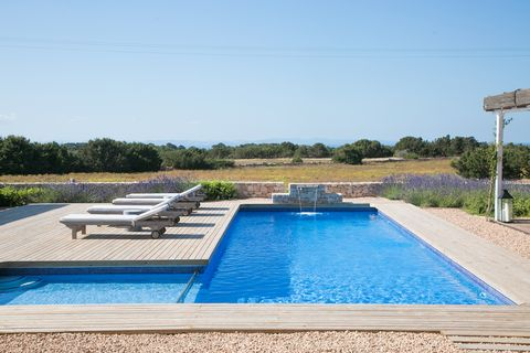 swimming pool with wooden platform and pebbles