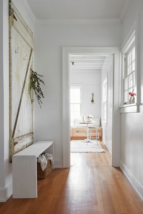hallway decorated with old barn door and white shoe bench