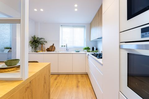 semi open kitchen designed in white with cupboards and drawers without handles