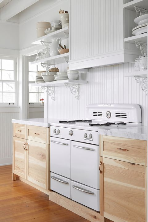chic farmhouse style kitchen decorated in white with wooden cabinets and marble countertops