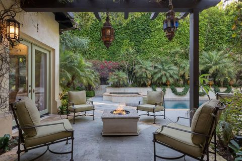 classic Mediterranean style porch with armchairs and outdoor fireplace
