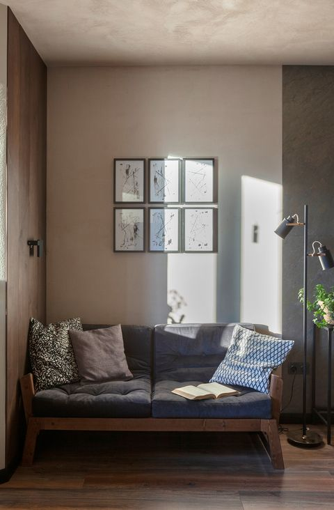 living room with plaster walls and a sofa in brown tones
