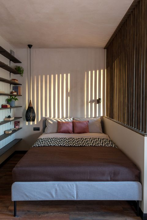 bedroom decorated in earth tones with wooden slats on the window