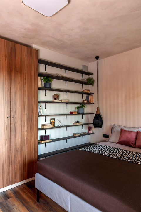 bedroom decorated in earth tones with open bookcase