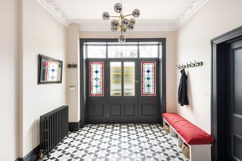 hall with hydraulic tiles, shoe rack and mid century lamp