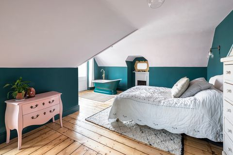 bedroom with freestanding bathtub and vintage dresser in pink