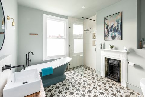 vintage bathroom with fireplace, classic freestanding bathtub and hydraulic tile floor