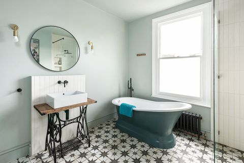 vintage bathroom with antique sewing machine, classic freestanding bathtub and hydraulic tile floor