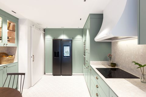 Provençal style office kitchen with dusty green cabinets and stainless steel fridge