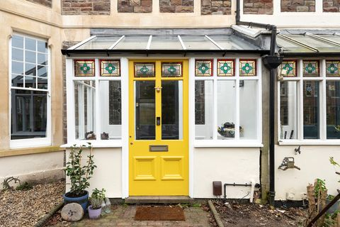 mudroom with yellow painted door and decorative stained glass