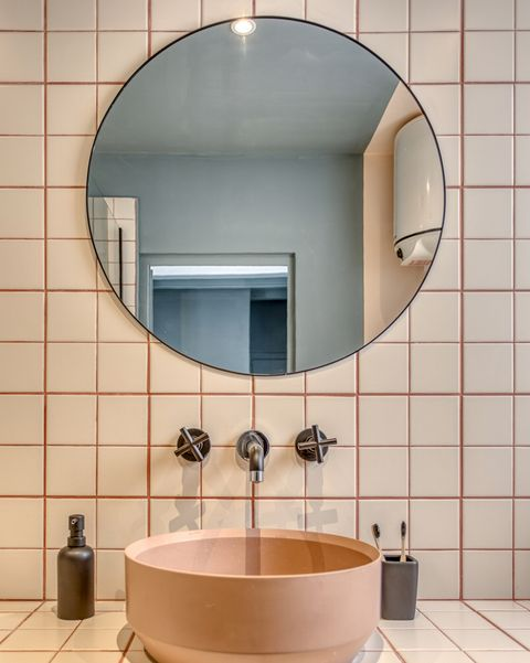 a cool vintage apartment in barcelona bathroom with freestanding sink and round mirror