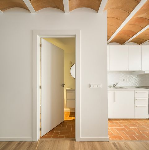 white designed kitchen next to bathroom