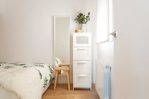 standing mirror, tall narrow white dresser, and wooden stool