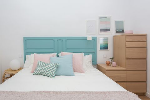 nordic style bedroom with turquoise blue painted door as a headboard