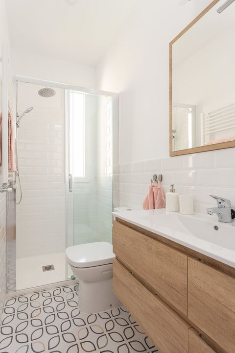 bathroom with walk-in shower and geometric tiles on the floor