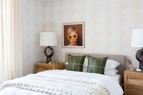 chic and feminine bedroom with wallpaper on the headboard wall