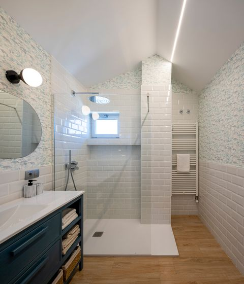 bathroom with walk-in shower with white subway tiles and wallpaper with fish