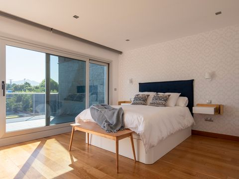bedroom decorated in neutral tones and blue details with wooden floor and wallpaper on the headboard wall