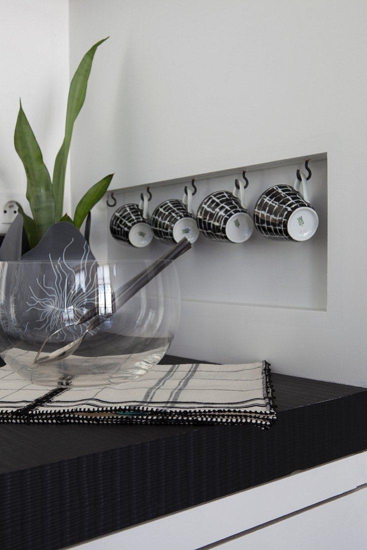Tassen hängen an Haken in einer kleinen Wandnische