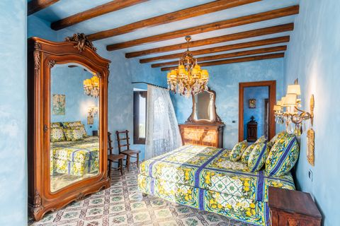bedroom decorated in blue with antique furniture and exposed wooden beams
