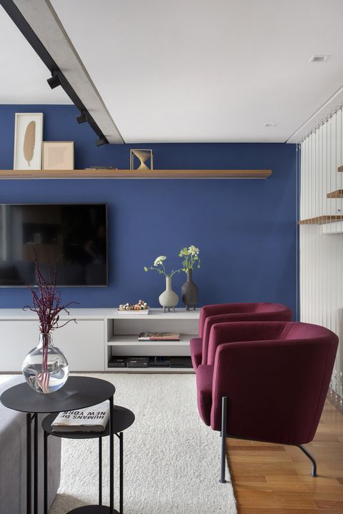 contemporary design lounge with burgundy velvet armchairs and blue painted wall