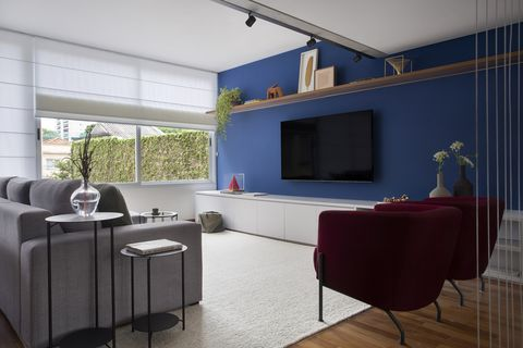 contemporary design living room with gray sofa, burgundy velvet armchairs and blue painted wall