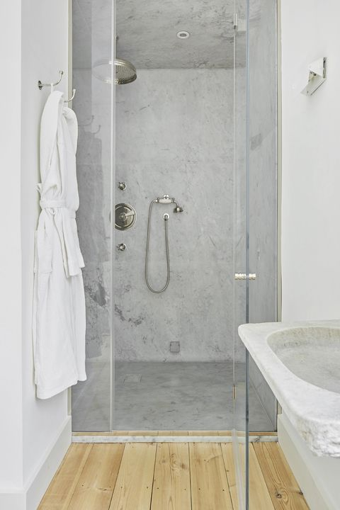 walk-in shower lined with marble and pine floor
