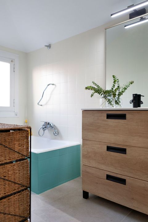 bathroom with bathtub lined with blue tiles